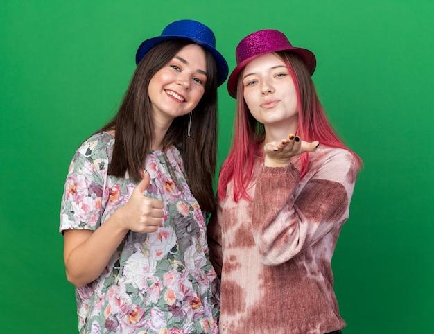 Glimlachende meisjes die feestmuts dragen die duim tonen en kusgebaar tonen dat op groene muur wordt geïsoleerd