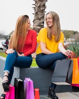 Glimlachende meisjes die met het winkelen zakken elkaar bekijken