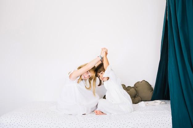 Glimlachende meisjes die op bed zitten