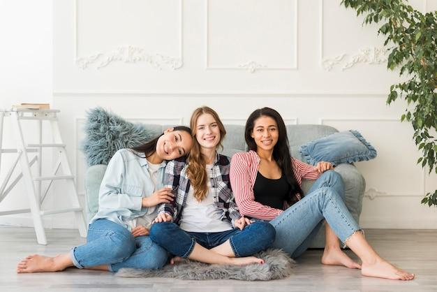 Glimlachende meisjes die op vloer met blootgestelde benen op blote voeten zitten