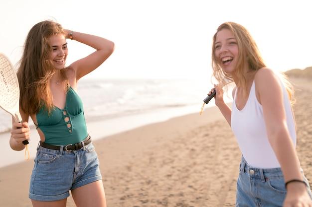 Glimlachende meisjes die tennisracket houden die bij strand genieten van