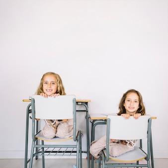 Glimlachende meisjes die van achter stoelen gluren