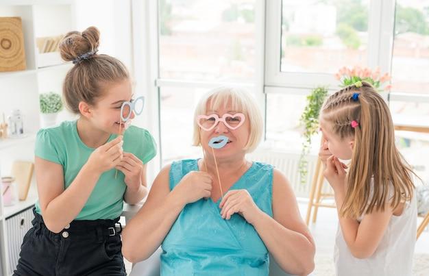 Glimlachende meisjes en hogere vrouw met document glazen en lippen in lichte ruimte