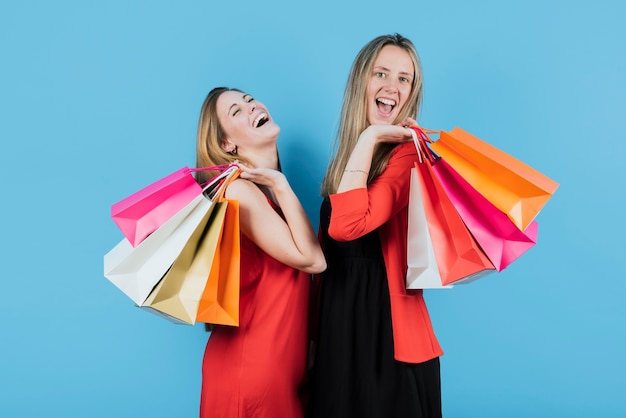 Glimlachende meisjes houden van boodschappentassen