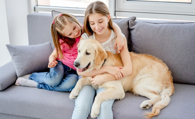 Glimlachende meisjes knuffelen mooie hond in lichte kamer