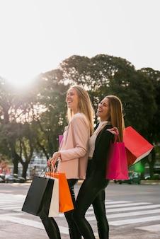 Glimlachende meisjes met boodschappentassen op straat