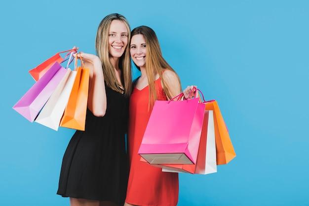 Glimlachende meisjes met boodschappentassen