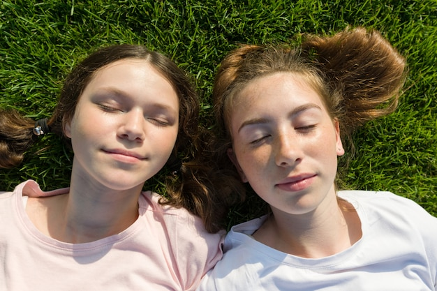 Glimlachende meisjes met gesloten ogen die op groen gras liggen.