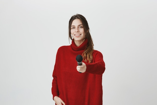 Glimlachende meisjesverslaggever die microfoon overhandigt