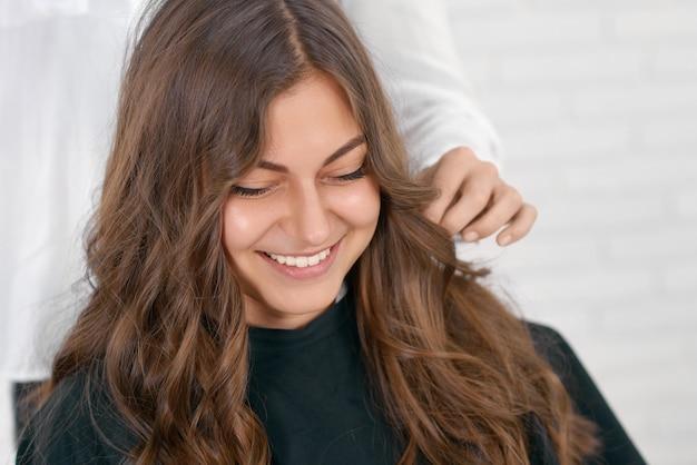 Glimlachende meisjeszitting in beaty salon, die op kapsel wachten.