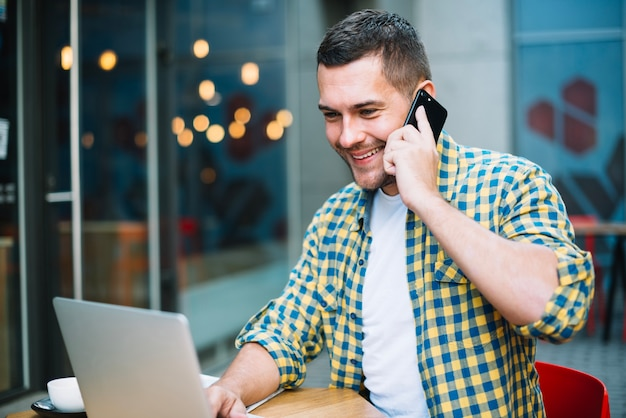 Glimlachende mens bij telefoon het ontspannen in cafetaria
