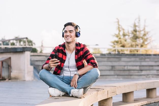 Glimlachende mens die aan muziek op hoofdtelefoon luistert