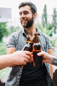 Glimlachende mens die bierflessen met het roosteren van zijn vrienden