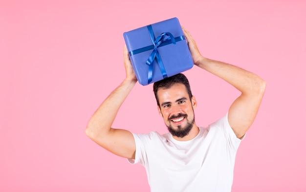 Glimlachende mens die blauwe verpakte giftdoos over zijn hoofd houdt tegen roze achtergrond