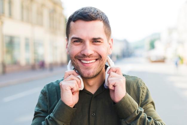 Glimlachende mens die de hoofdtelefoon van de cameraholding rond zijn hals bekijken