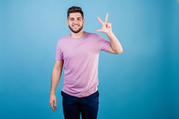 Glimlachende mens die drie vingers toont die op blauw worden geïsoleerd