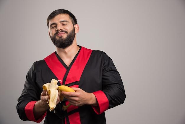 Glimlachende mens die een banaan op grijze muur eet.