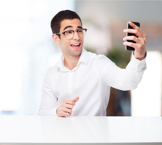 Glimlachende mens die een foto met zijn mobiele telefoon