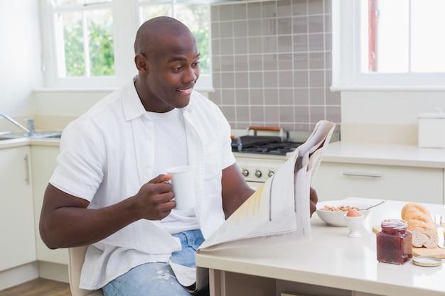 Glimlachende mens die een krant leest en thee drinkt
