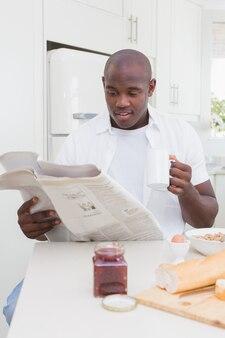 Glimlachende mens die een krant leest en zijn ontbijt neemt