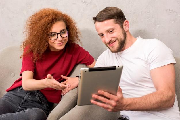 Glimlachende mens die iets toont aan zijn vriend op digitale tablet