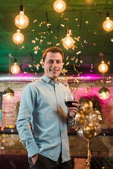Glimlachende mens die in de wijnglas van de partijholding geniet van