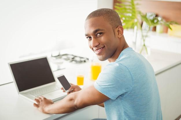 Glimlachende mens die laptop en smartphone in de woonkamer thuis met behulp van