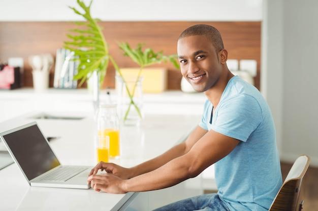 Glimlachende mens die laptop thuis met behulp van