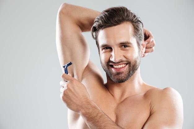 Glimlachende mens die met scheermes aan camera glimlacht