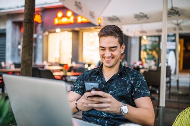 Glimlachende mens die mobiele telefoon in caf� met behulp van