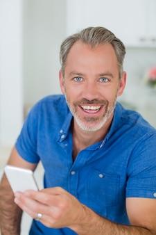 Glimlachende mens die mobiele telefoon in keuken houdt