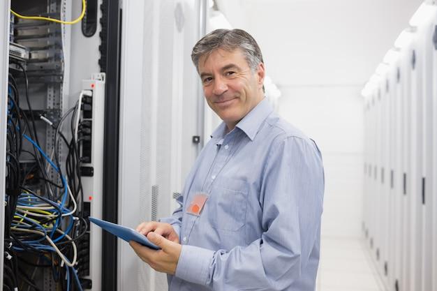 Glimlachende mens die onderhoud op servers doet