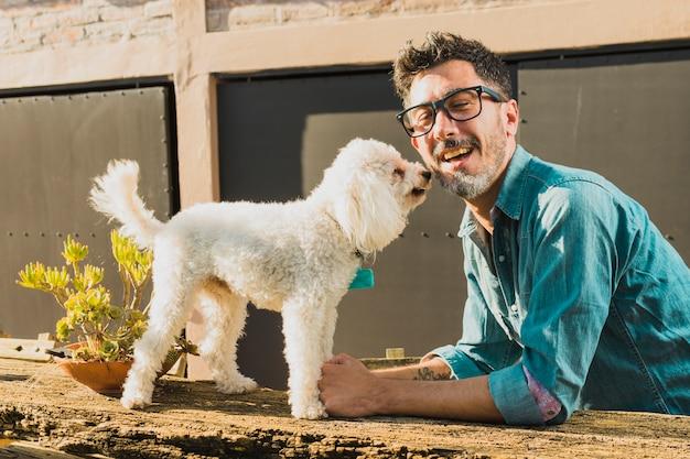 Glimlachende mens die oogglazen draagt die wit puppy spelen