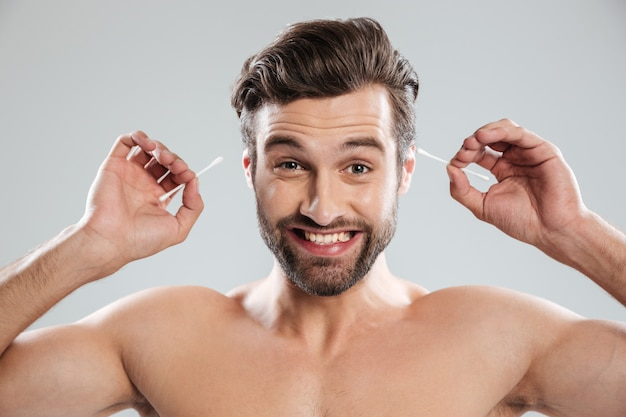 Glimlachende mens die oorstokken gebruikt