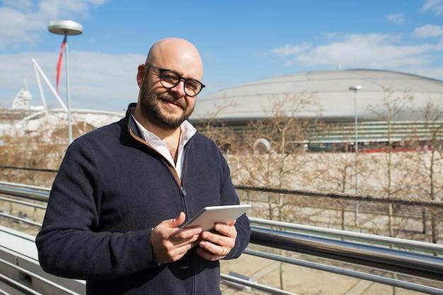 Glimlachende mens die op middelbare leeftijd tablet in openlucht gebruikt