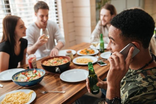 Glimlachende mens die op mobiele telefoon spreekt en met vrienden viert