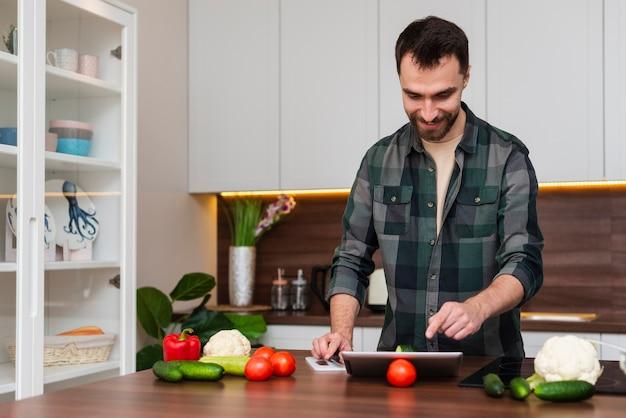 Glimlachende mens die op tablet in keuken kijkt