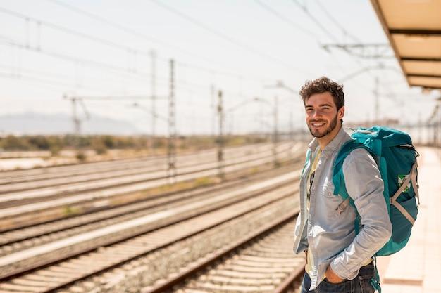Glimlachende mens die op trein wacht