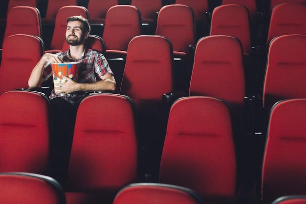 Glimlachende mens die popcorn in bioskoop eet