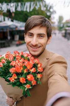 Glimlachende mens die selfie met bloemen maken