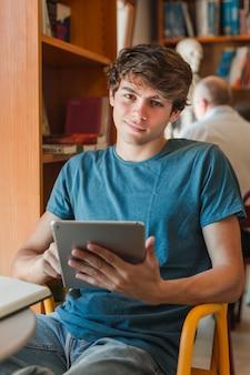 Glimlachende mens die tablet gebruikt