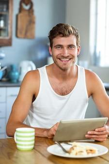 Glimlachende mens die tabletpc met behulp van bij ontbijtlijst
