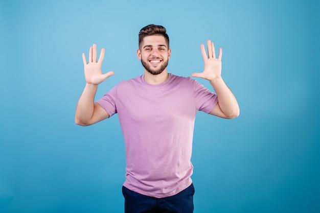 Glimlachende mens die tien vingers toont die op blauw worden geïsoleerd