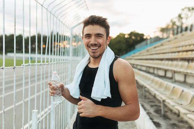 Glimlachende mens die witte handdoek en fles water houdt.