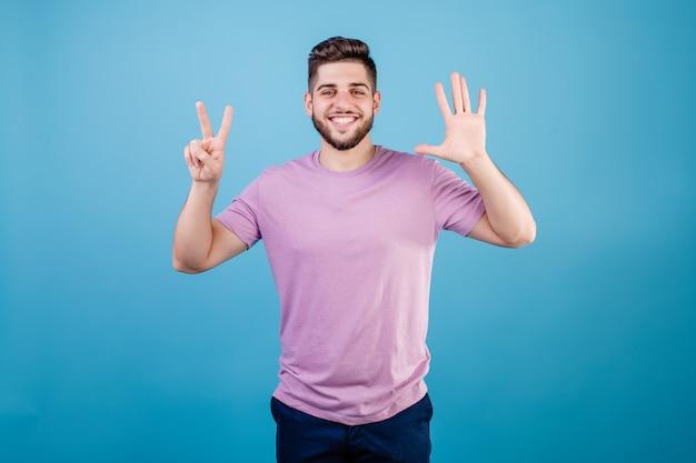 Glimlachende mens die zeven vingers toont die op blauw worden geïsoleerd