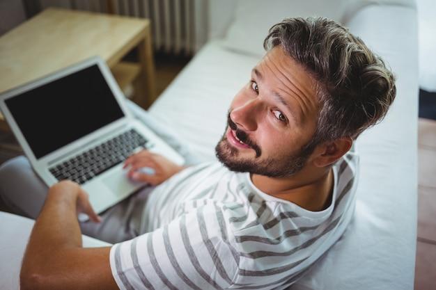 Glimlachende mens die zijn laptop in woonkamer met behulp van