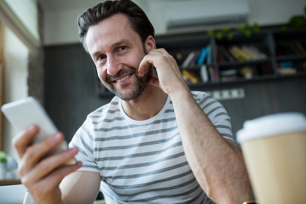Glimlachende mens die zijn mobiele telefoon in de koffiebar