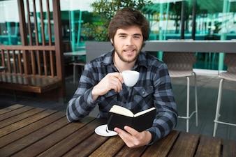 Glimlachende mens het drinken koffie en het lezen van dagboek in straatkoffie