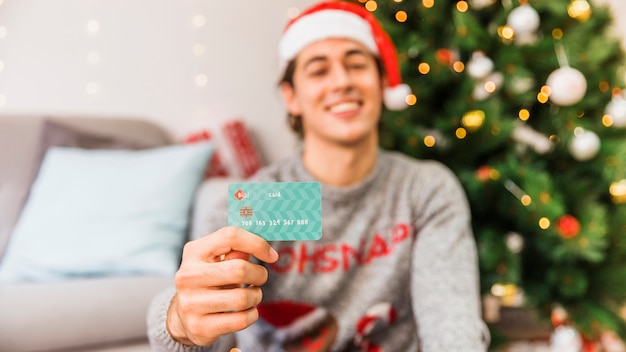 Glimlachende mens in de holdingscreditcard van de kerstmanhoed