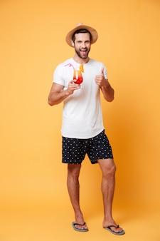 Glimlachende mens in de zomerhoed met cocktail die camera kijken